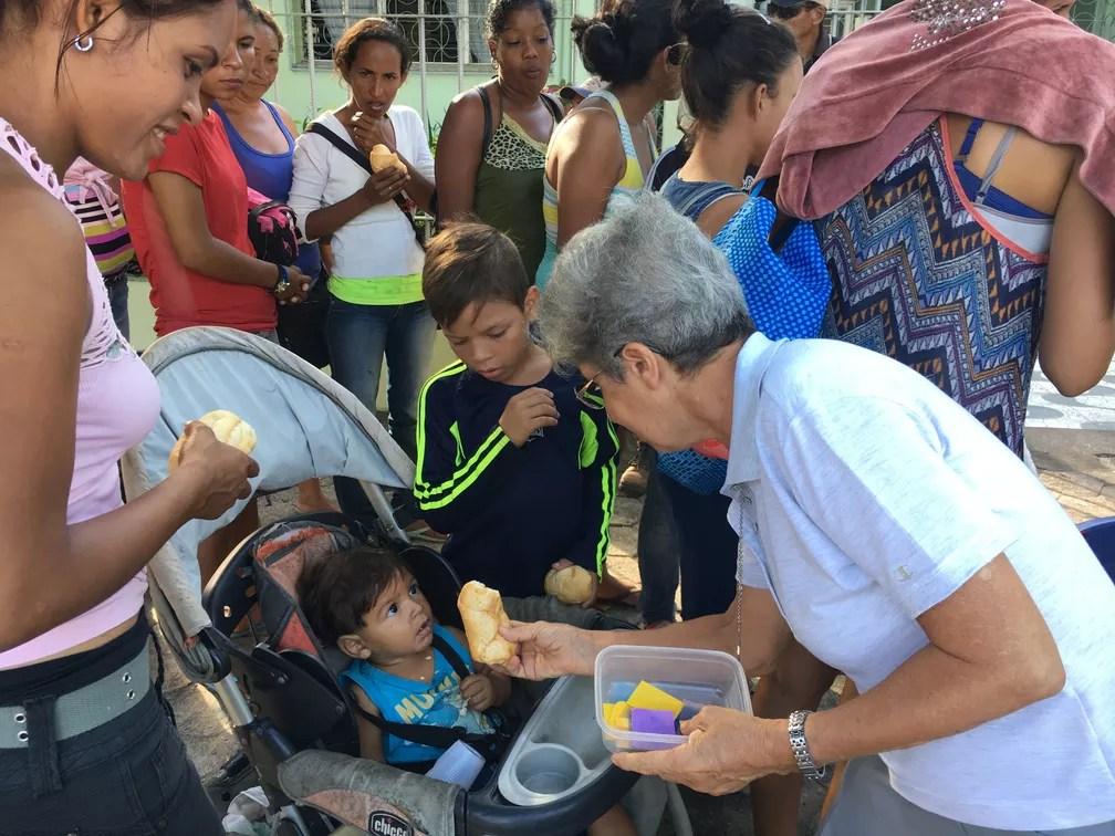 Irmã Elisa Pandiani entrega pães a crianças refugiadas venezuelanas no Centro de Boa Vista — Foto: Emily Costa/G1 RR
