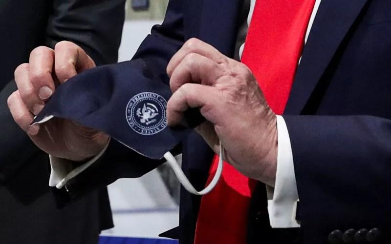 O presidente dos EUA, Donald Trump, segura uma máscara com o selo presidencial que disse ter usado durante visita à fábrica de componentes da Ford em Ypsilanti, Michigan, em 21 de maio — Foto: Reuters/Leah Millis