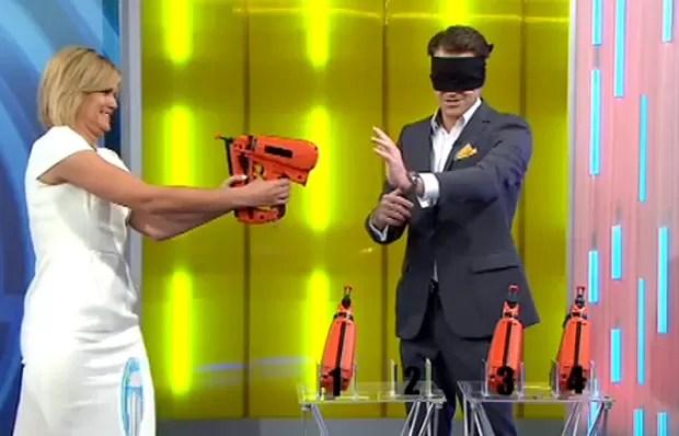 Apresentadora quase entrou em enrascada ao apontar arma de pregos contra o próprio rosto (Foto: Reprodução/YouTube/Studio 10)