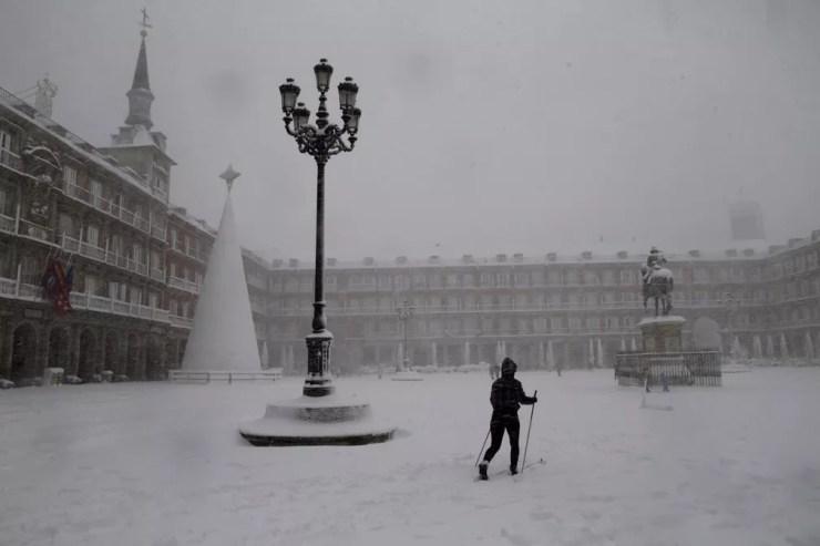 Uma mulher esquia ao cruzar a Plaza Mayor em Madrid durante uma forte nevasca — Foto: Andrea Comas/AP Photo
