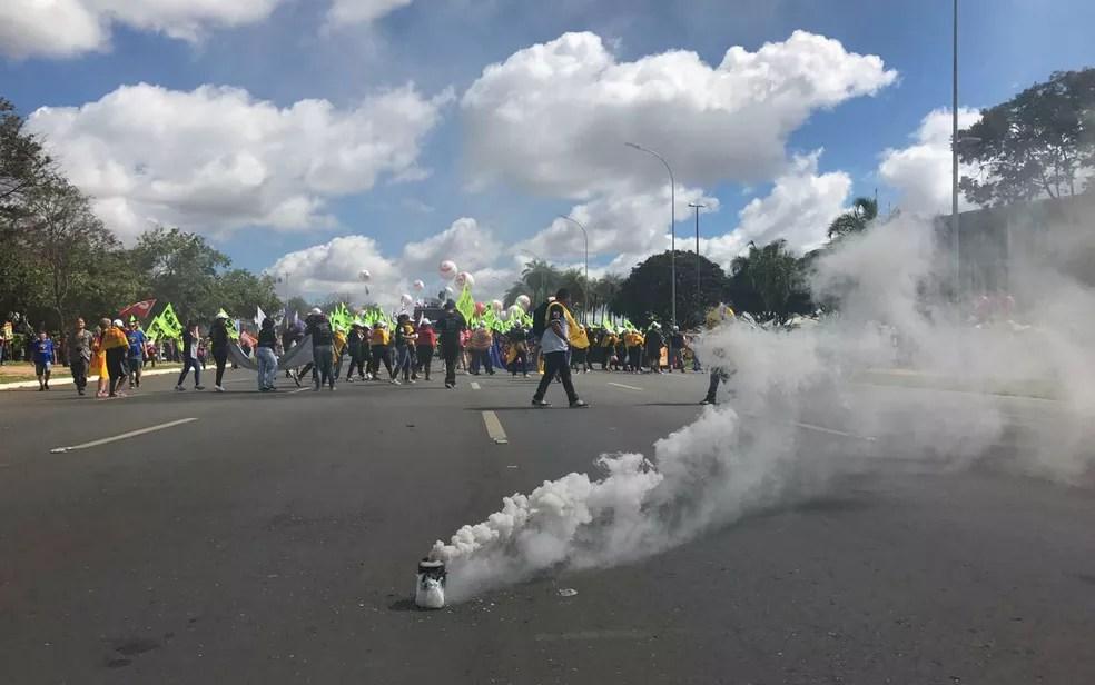 Manifestantes soltam bomba de fumaça na N1, no Eixo Monumental, durante ato contra governo Temer (Foto: Letícia Carvalho/G1)