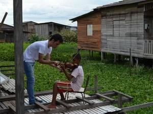 Lucas Nunes, violonista da orquestra Camerata, passando instruções para criança da comunidade (Foto: Denise Muniz/G1)