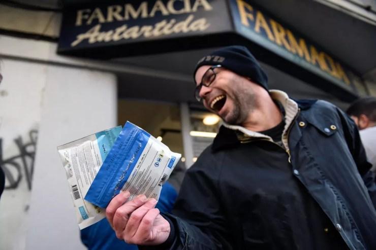 Juan Zas exibe dois pacotes de maconha legal comprados em uma farmácia do centro de Montevidéu, no Uruguai. A maconha está sendo vendida em 16 farmácias do país, o último passo na aplicação de uma lei de 2013 que fez o Uruguai legalizar o mercado de maconha cobrindo toda a cadeia de produção, da plantação à venda (Foto: Matilde Campodonico/AP)