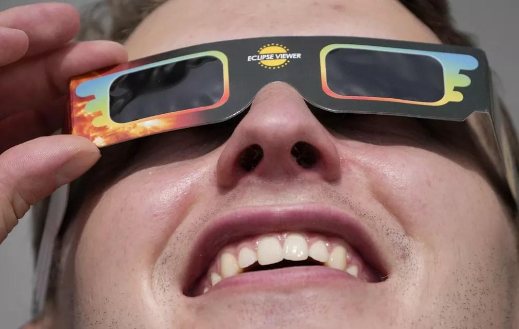 Homem usa óculos especiais para assistir eclipse em Trafalgar Square, Londres, nesta quinta-feira (10) — Foto: Frank Augstein/AP