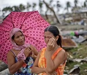 Mulher chora ao encontrar os corpos da mãe e da irmã sob escombros no centro de Tacloban, a cidade mais destruída pela passagem do supertufão Haiyan nas Filipinas (Foto: AP Photo/Dita Alangkara)