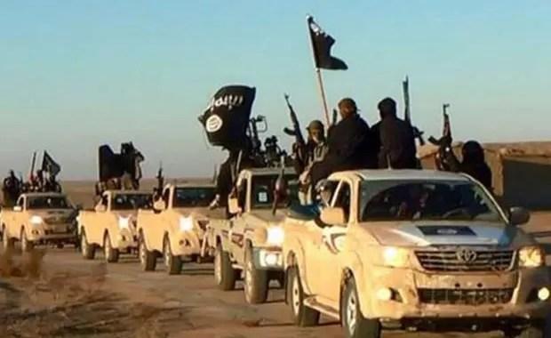 Jihadistas do Estado Islâmico exibem suas armas e bandeiras do grupo em comboio em uma estrada de Raqqa, na Síria, em maio de 2015  (Foto: Militant website via AP)