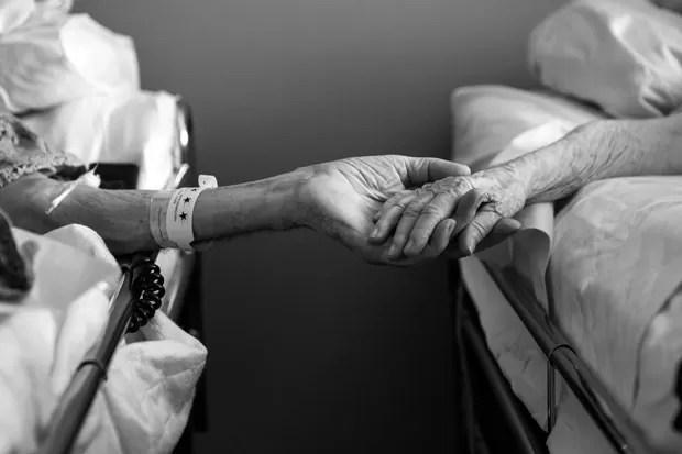 Don e Maxine Simpson são vistos de mãos dadas em camas de hospital em julho de 2014. Eles morreram com apenas quatro horas de diferença após 62 anos de casamento (Foto: Melissa Sloan/AP)