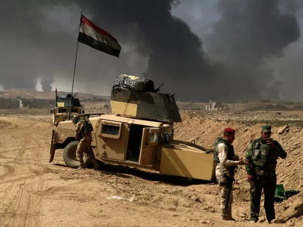 Soldados iraquianos são vistos perto da fronteira de Qayyarah, onde a fumaça sobe de campos de petróleo incendiados por integrantes do Estado Islâmico, na terça (4) (Foto: AP Photo/Bram Janssen)