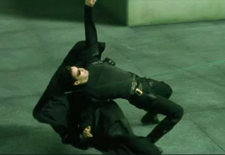 Neo, interpretado por Keanu Reeves em 'Matrix', defende-se de disparos