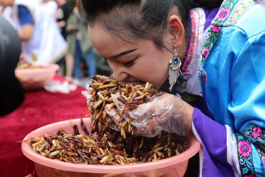 26 de junho - Mulher usa luvas para encher a boca de insetos em uma competição para ver quem consegue comer mais insetos promovida em um ponto turístico de Lijiang, na província de Yunnan, na China (Foto: Reuters/Stringer)