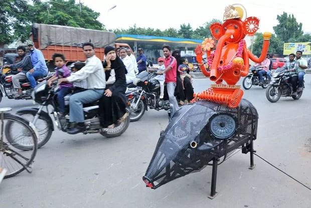 Um designer indiano criou robô em formato de rato usando peças de carros usados. A máquina anda sozinha e carrega uma estátua também feita de sucata do deus hindú Ganesha  (Foto: AFP)