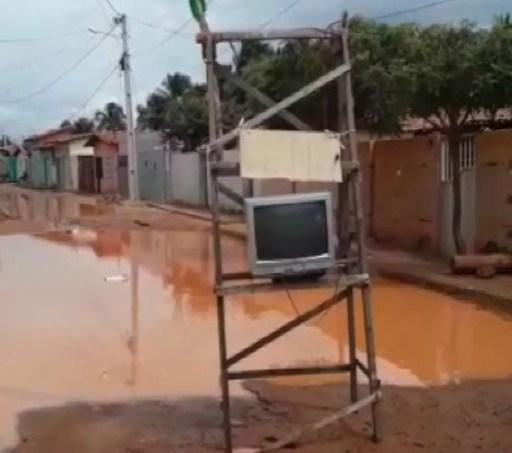 Moradores montam sala de TV em meio à rua alagada em Touros  (Foto: Reprodução )
