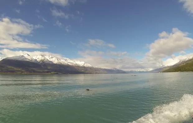 Barco segue em alta velocidade ao lado de paisagem de montanhas com neve (Foto: Juliana Cardilli/G1)