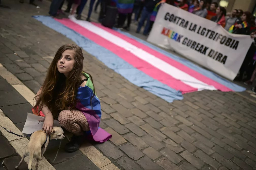 Uma mulher brinca com um cachorro enquanto participa de um protesto em apoio a pessoas transexuais que lutam por seus direitos, durante uma manifestação que celebra o Dia Internacional contra Homofobia, Transfobia e Bifobia, em Pamplona, na Espanha (Foto: Alvaro Barrientos/AP)