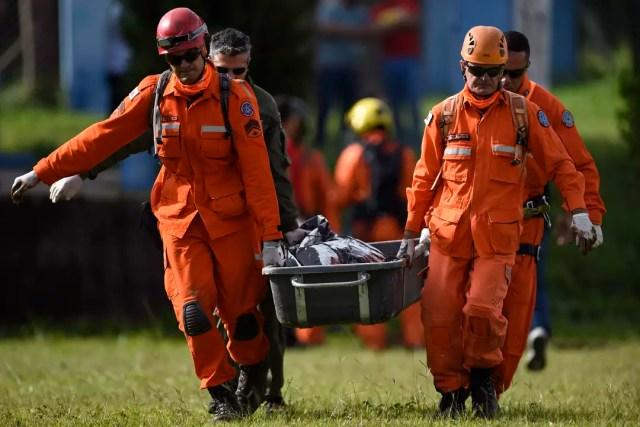 Bombeiros carregam corpo resgatado em Brumadinho
