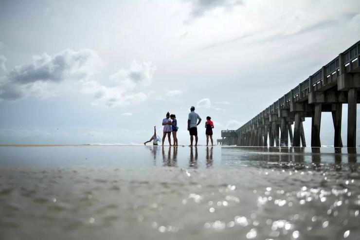 Pessoas caminham em Panama City Beach, na Flórida, na terça-feira (9), antes da chegada do furacão Michel  — Foto: Brendan Smialowski / AFP