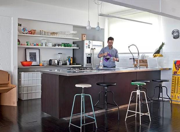Azulejos vintage revestem a cozinha do arquiteto Mauricio Arruda, que tem bancada com bancos de farmácia. É lá mesmo que ele recebe os amigos. Utensílios para cozinhar e servir ficam expostos em prateleiras (Foto: Lufe Gomes/Casa e Jardim)