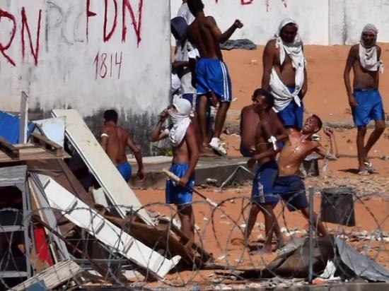 19/01 - Presos atiram pedras durante um confronto de facções na penitenciária de Alcaçuz, perto de Natal, no Rio Grande do Norte (Foto: Josemar Gonçalves/Reuters)