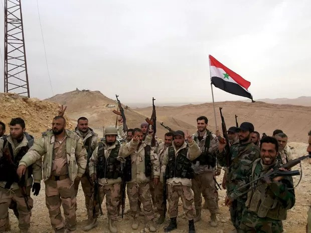 Forces loyal to Syria's President Bashar al-Assad flash victory signs and carry a Syrian national flag on the edge of the historic city of Palmyra in Homs Governorate, in this handout picture provided by SANA on March 26, 2016. (Foto: SANA/Reuters)