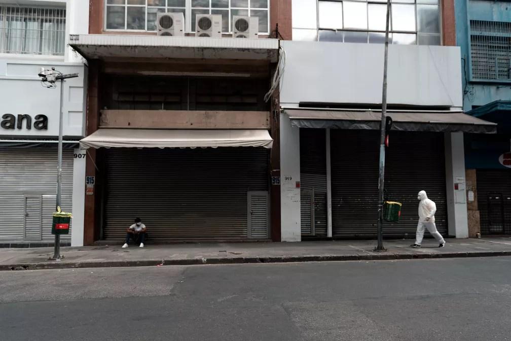 SÃO PAULO - Pessoas passam pela rua 25 de março, em São Paulo, com o comércio fechado nesta sexta-feira (20) para evitar a propagação do novo coronavírus — Foto: Marcelo Brandt/G1