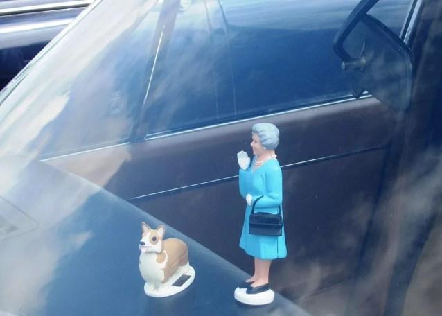 Elizabeth II e um de seus corgis: adorno de carro mostra que os cães se tornaram uma marca registrada da realeza (Foto: https://commons.wikimedia.org/wiki/File:Jaguar_XJ_3.4_containing_Queen_n_%27Corgi_dashboard_ornament._The_ornament.JPG)