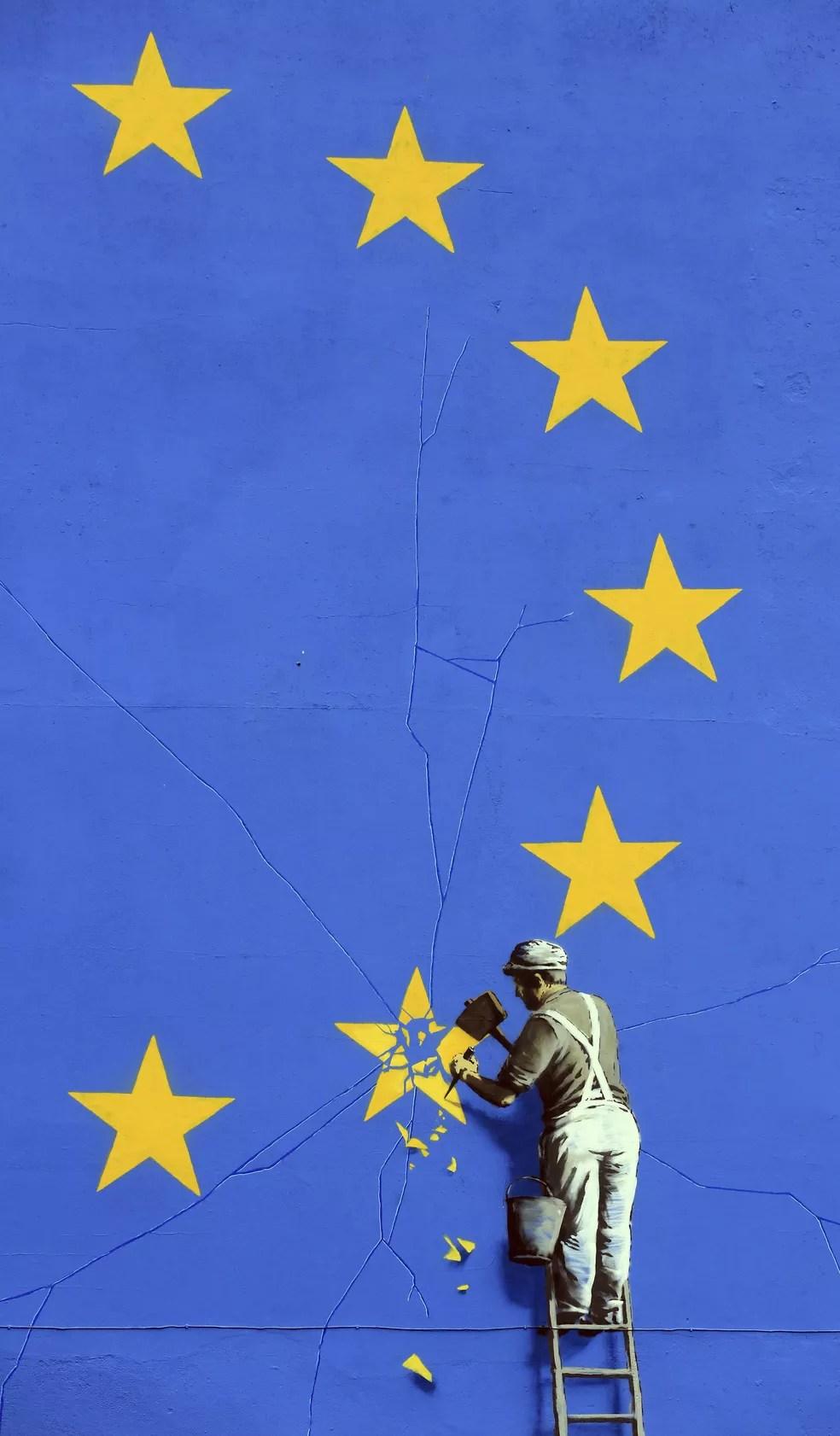 Pintura mostra trabalhador sobre escada, eliminando com martelo uma das estrelas da bandeira da União Europeia (Foto: Gareth Fuller/via AP)
