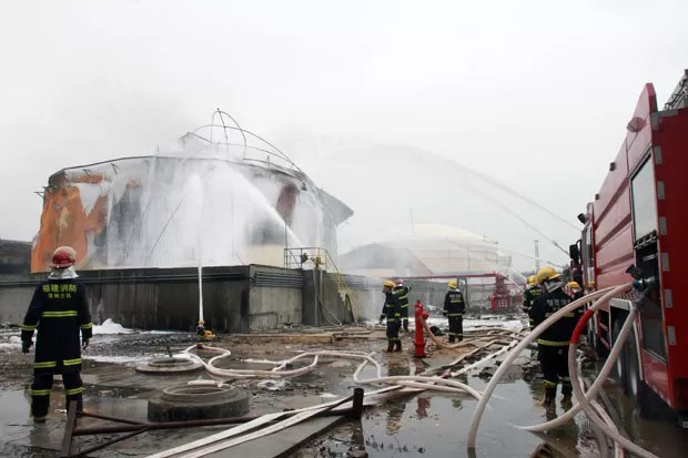 Bombeiros trabalham em tanque de produtos químicos que pegou fogo em fábrica na China nesta quinta-feira (9) (Foto: AFP)