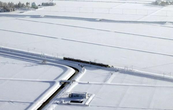 Foto aérea mostra o trem de quatro vagões atolado na neve em Sanjo, na região de Niigata, no Japão  (Foto: Kyodo/via Reuters)