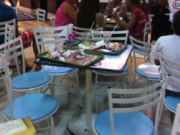 Pessoas deixam bandejas com restos de comida em cima das mesas de praça de alimentação de shoppings de Maceió (Foto: Fabiana De Mutiis/G1)