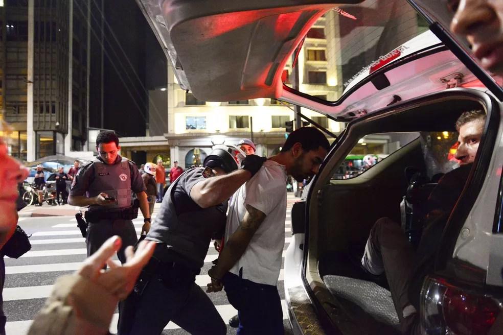 Homem é detido na Avenida Paulista, em São Paulo, após confronto durante protesto de contrários e favoráveis à Lei de Migração no Brasil na noite de terça-feira (2) (Foto: Cris Faga/Fox Press Photo/Estadão Conteúdo)