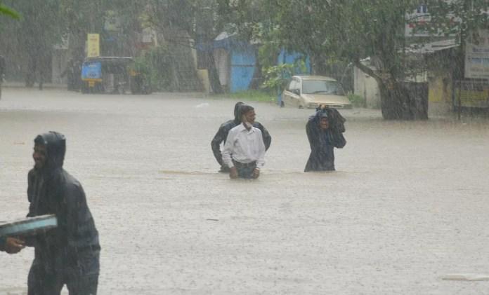 Pessoas atravessam área alagada em Kolhapur, no estado de Maharashtra, em 23 de julho de 2021. Deslizamentos de terra provocados pelas fortes chuvas de monções deixaram dezenas de mortos e desaparecidos no oeste da Índia. — Foto: AP