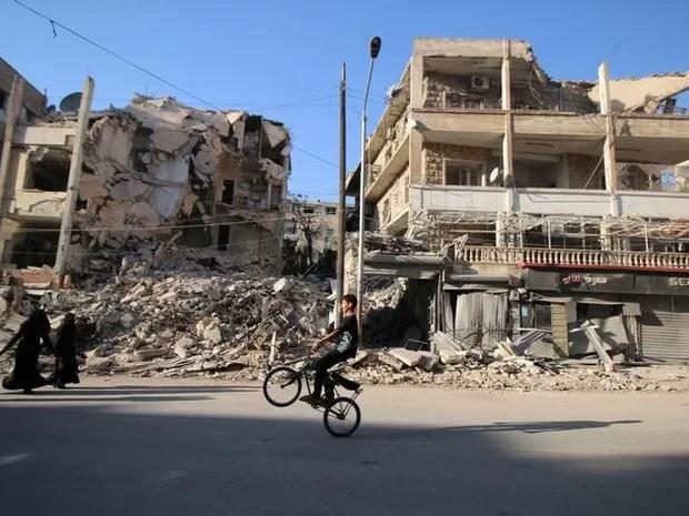 Garoto anda de bicicleta nesta quinta-feira (6) diante de edifícios destruídos em Aleppo (Foto: REUTERS/Abdalrhman Ismail)