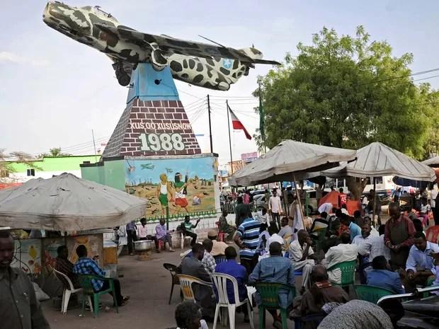 Moradores sentam em frente a monumento com avião russo que foi usado em 1988, em Hargeisa, na Somalilândia (Foto: MOHAMED ABDIWAHAB / AFP)