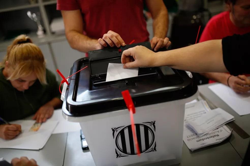 Mulher coloca seu voto em urna em escola em Sant Julia de Ramis que serviu de local de votação do referendo que decidiu por independência da Catalunha (Foto: Francisco Seco/AP)