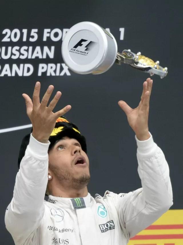 Lewis Hamilton joga troféu para o alto no pódio do GP da Rússia (Foto: AFP)