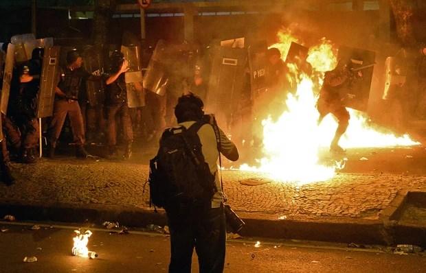 Coquetel molotov atinge um dos policiais (Foto: Tasso Marcelo/AFP)