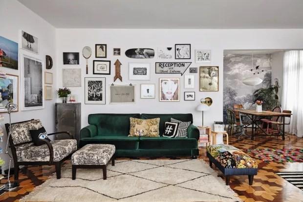 A sala mostra a parede com raquete de Felipe Morozini, skate de Vavá Ribeiro, seta e gabinete garimpados em flea markets de NY.  No estar, pufe revestido com bordados antigos needlepoint, tapete latino-americano. Abajur e, sobre o sofá, almofadas (Foto: Victor Affaro / Editora Globo)