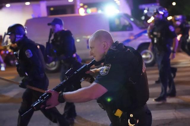 Policiais são vistos em ação após um deles ser baleado durante manifestação em Louisville, Kentucky, na quarta-feira (23) — Foto: AP Foto/John Minchillo