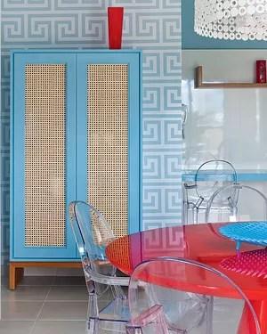 A marcenaria também foi adaptada no projeto da arquiteta Andrea Murao e foi revestida de Formica, em vez de madeira laqueada. A palha dá respiro aos armários. As cadeiras de acrílico também são práticas para o apartamento em Ubatuba (Foto: Victor Affaro/Casa e Jardim)