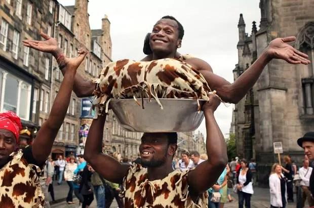 'Homem-borracha' é carregado em bacia, nesta sexta-feira, no festival Edinburgh Fringe, maior celebração artística anual do mundo. (Foto: David Cheskin/AP)