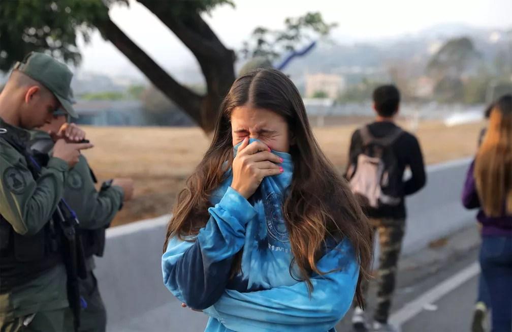 Mulher cobre o rosto após respirar gás lacrimogêneo atirado por militares da base aérea 'La Carlota', em Caracas — Foto: Manaure Quintero/Reuters