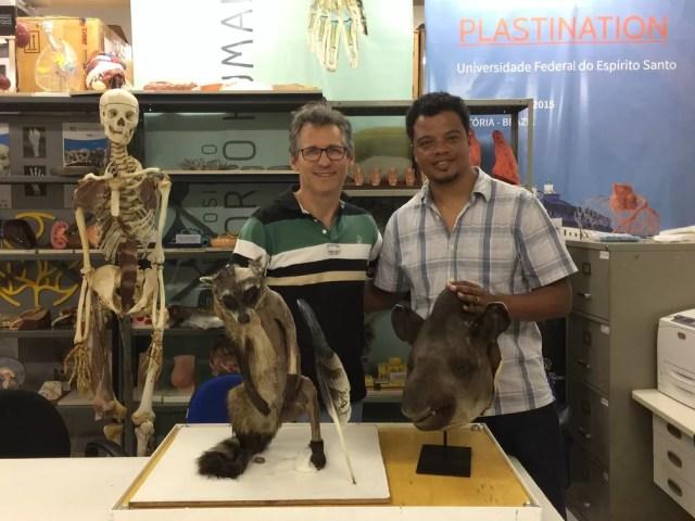 Athelson Bittencourt e Aureo Banhos no Laboratório de Plastinação do Museu de Ciências da Vida da Ufes. Um mão-pelada, com metade do corpo dissecado no plano muscular, e uma cabeça de anta. (Foto: Athelson Bittencourt / Arquivo pessoal)