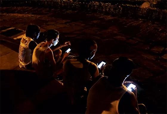 Rapazes usam celular para entrar na internet  (Foto: Desmond Boylan/AP)