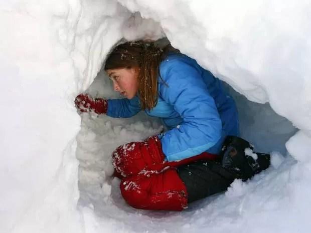 Jovem cava uma 'toca' sob a neve que caiu em Maplewood, Nova Jersey. (Foto: Rich Schultz / AP Photo)