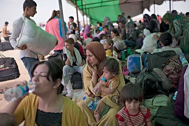 2. Gulchin, a mulher no centro, com o filho no colo, espera para embarcar em um ônibus (Foto: Lynsey Addario/The New York Times)