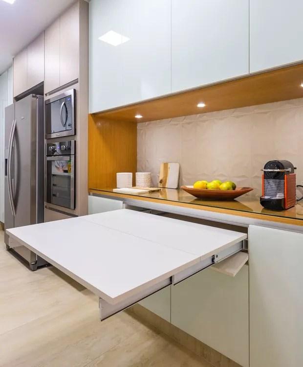 Os móveis da cozinha foram projetados para trazer praticidade, o armário, por exemplo, vira uma mesa para refeições rápidas. O revestimento é da Portobello. Os armários foram projeto da arquiteta.  (Foto: Fernando Crescenti/Divulgação)