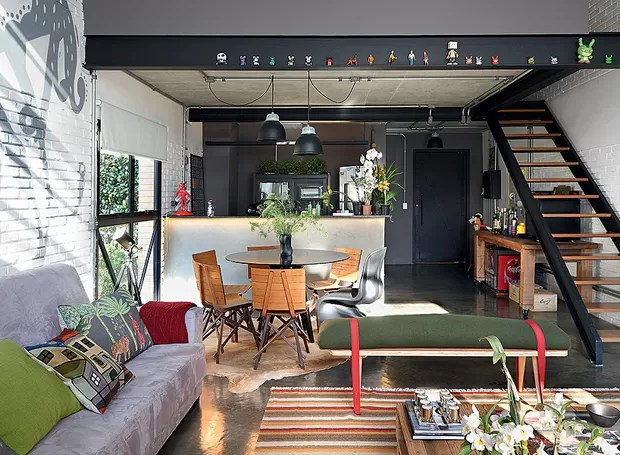 A cozinha americana fica logo na entrada do apartamento com decoração da arquiteta Bruna Riscalli. A marcenaria segue o tom escuro das paredes, dando um visual masculino e moderno (Foto: Evelyn Müller/Casa e Jardim)