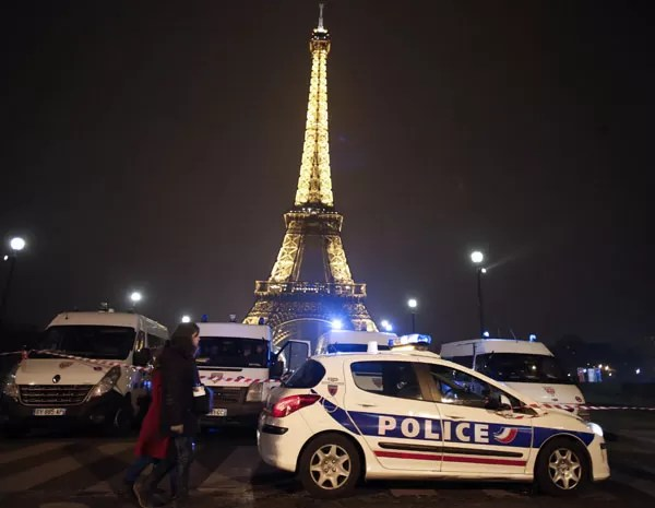 Pessoas passam por carros de polícia que bloqueiam o caminho para a Torre Eiffel Tower, neste sábado (30), após ameaça de ataque ao monumento. (Foto: Thomas Coex/ AFP Photo)