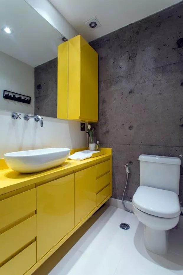 O banheiro recebeu piso mineral, cor off white, da Portobello.  Gabinete em laca amarela executado pela Marcenaria Maple. Torneira da Deca (Foto: Gustavo Awad/Divulgação)