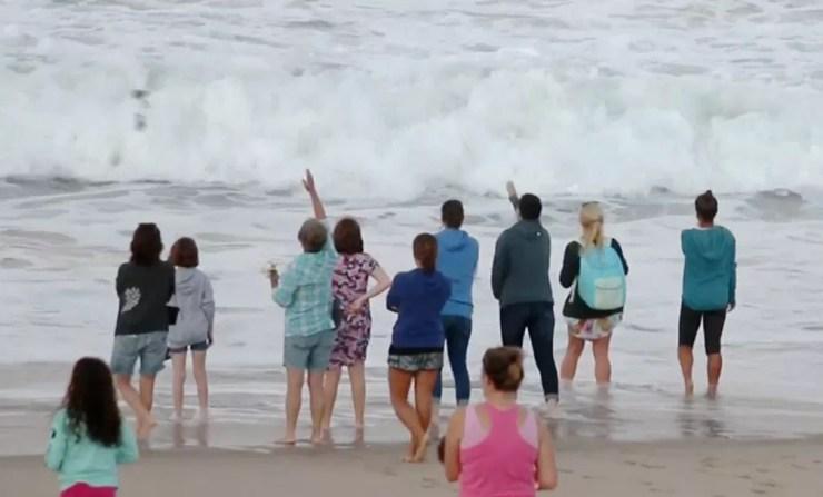 Pessoas jogam flores ao mar em homanegem a brasileiro morto em ataque de tubarão no último sábado em praia de Massachussetts, nos EUA — Foto: Reprodução/NBC